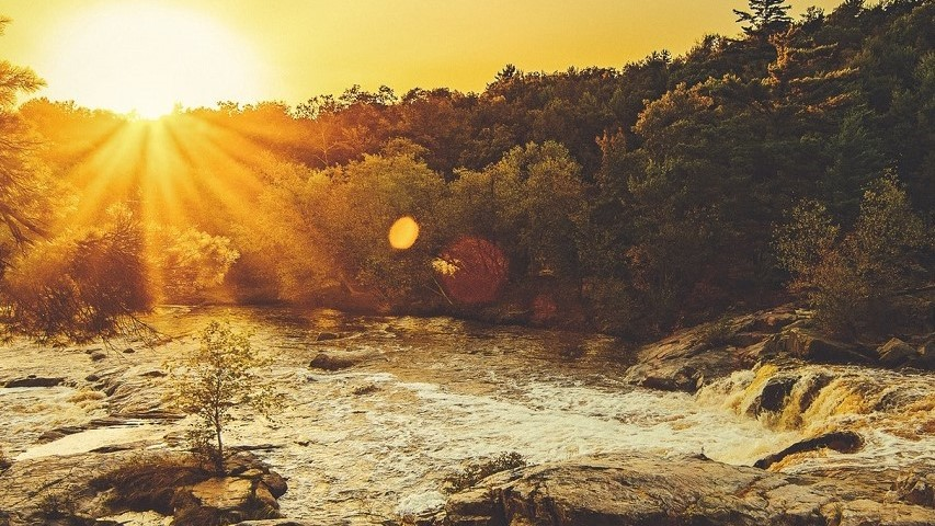 a picture of a river with trees in the background and the sun going down