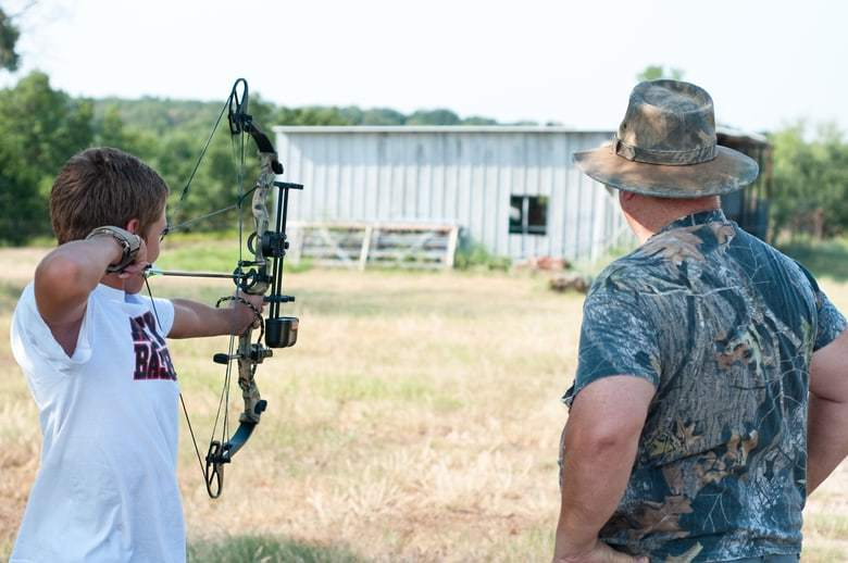 a man watching his son shooting a bow