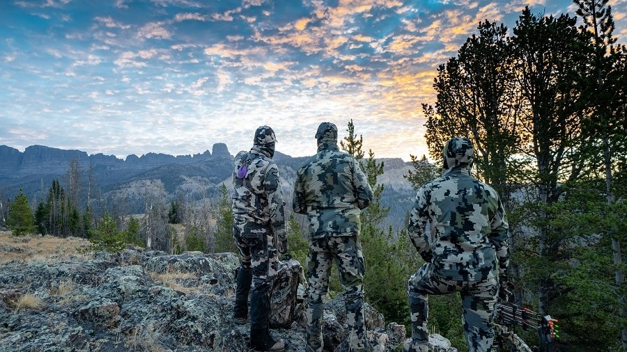 three bowhunters looking into a valley