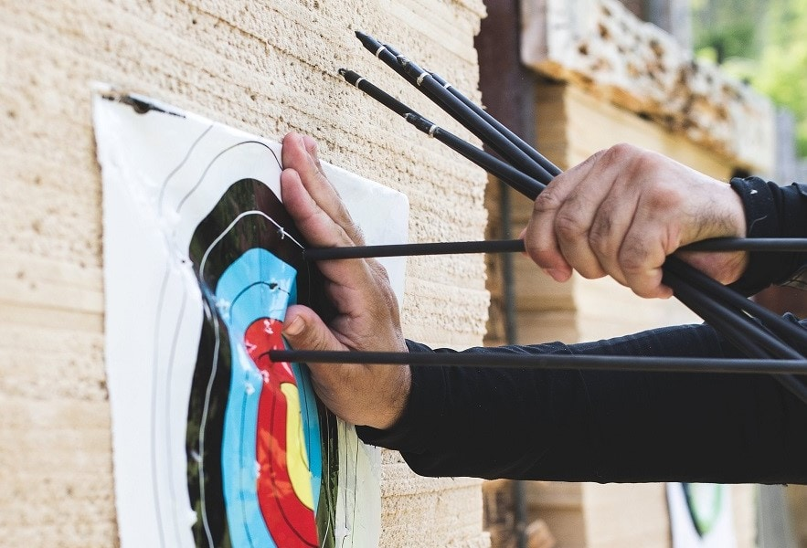 someone pulling arrows out of a target