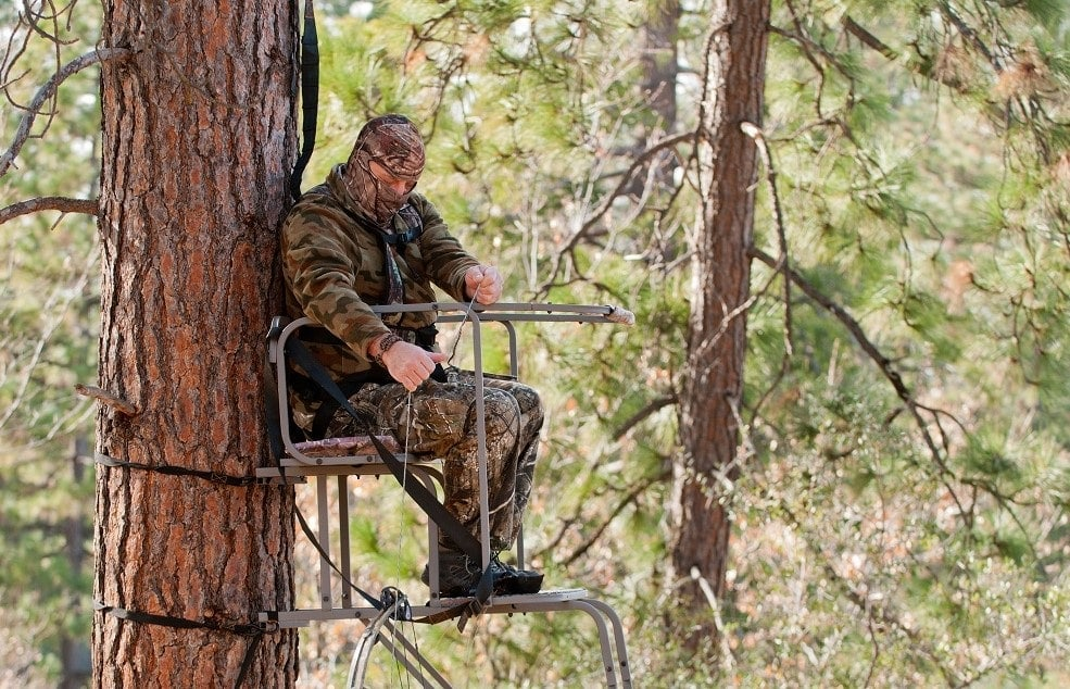 Bow hunter in a ladder style tree stand safely raising his bow with a haul line