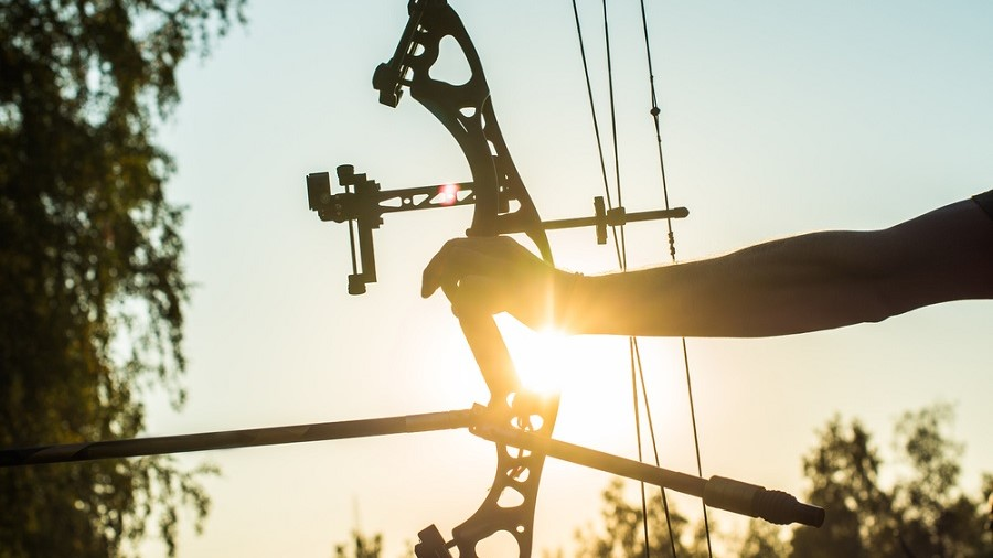 a compound bow held with one hand with the sun shining