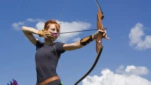 a woman aiming with a recurve bow