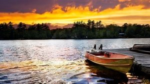 a boat on the lake with the sun going down