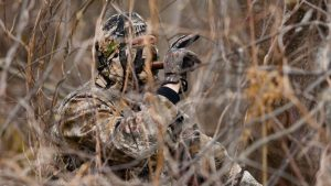 a hunter using a turkey call hiding in a bush