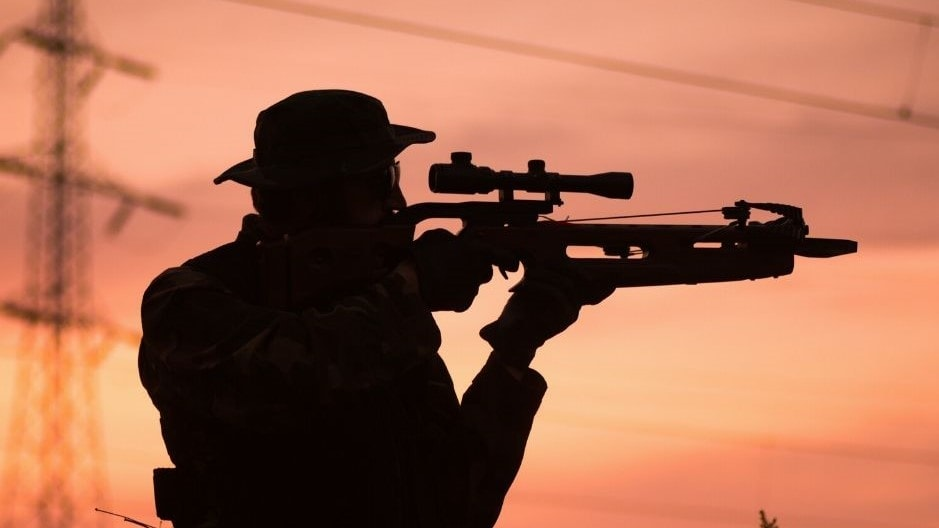 a man aiming his crossbow in dawn