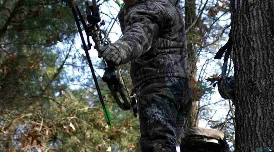 a man shooting from his climbing treestand