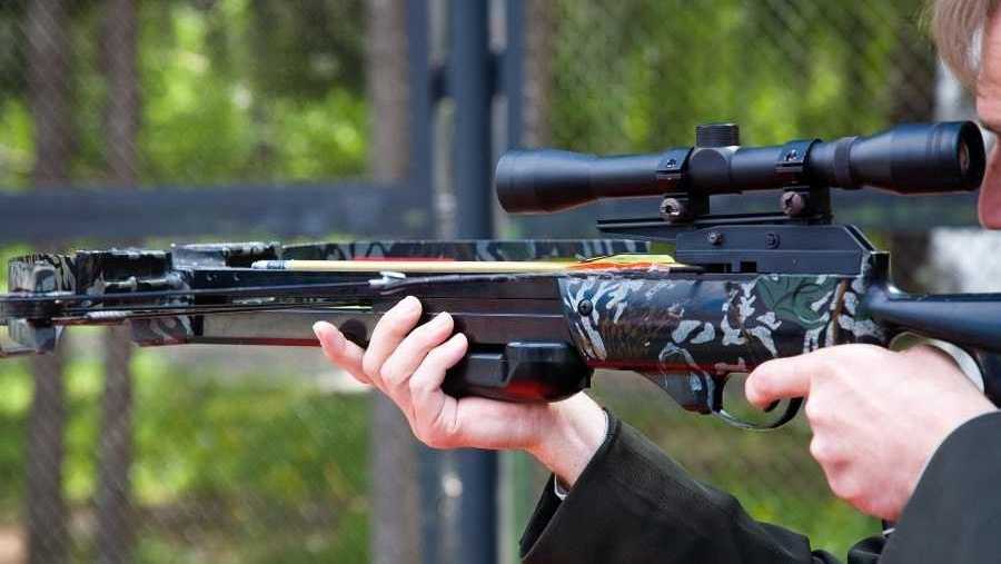 someone aiming with a crossbow and scope