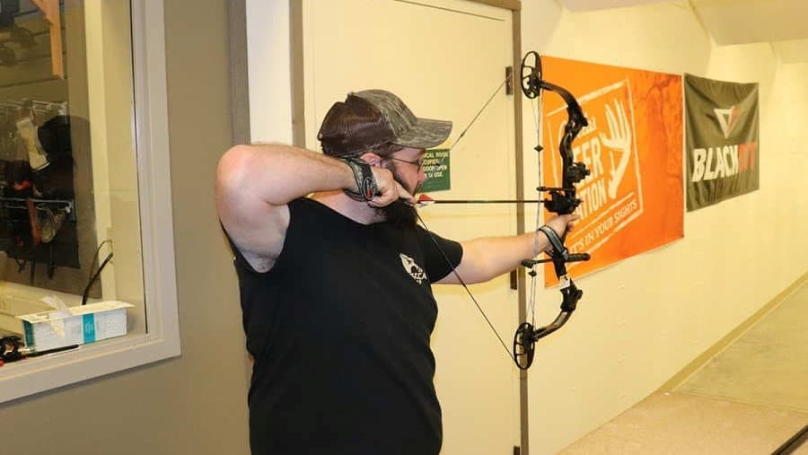 man shooting a compound bow