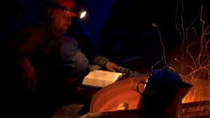 Man reading a map with headlamp
