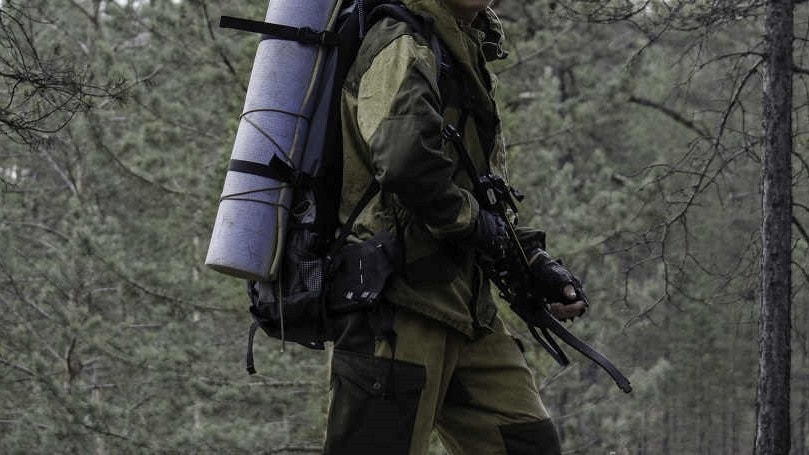 Hunter with crossbow walking with a backpack