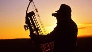 a bow hunter in the sunset using his binoculars