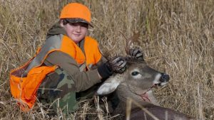 a young hunter posing with the deer he took with his bow