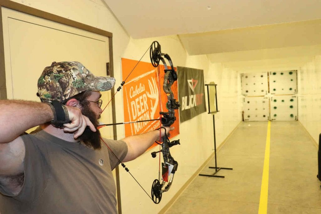 man shooting a compound bow indoors