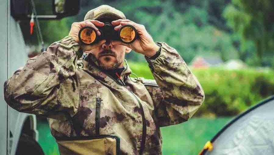 a hunter in camo looking through his binoculars