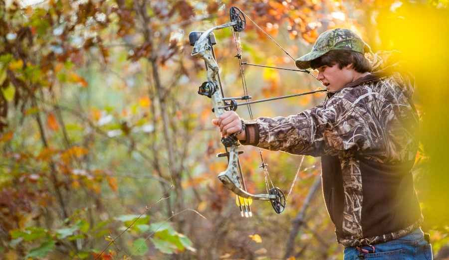 a boy shooting a compoundbow in the woods