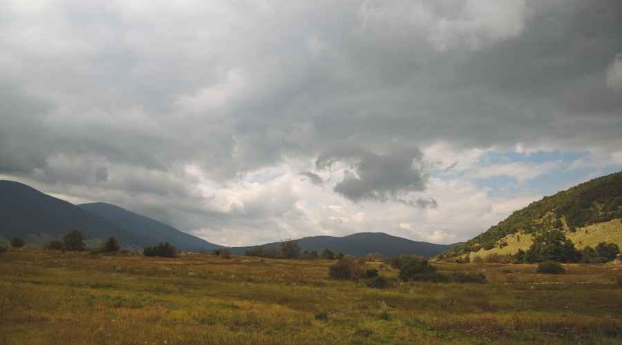 a landscape with hills and a cloudy sky
