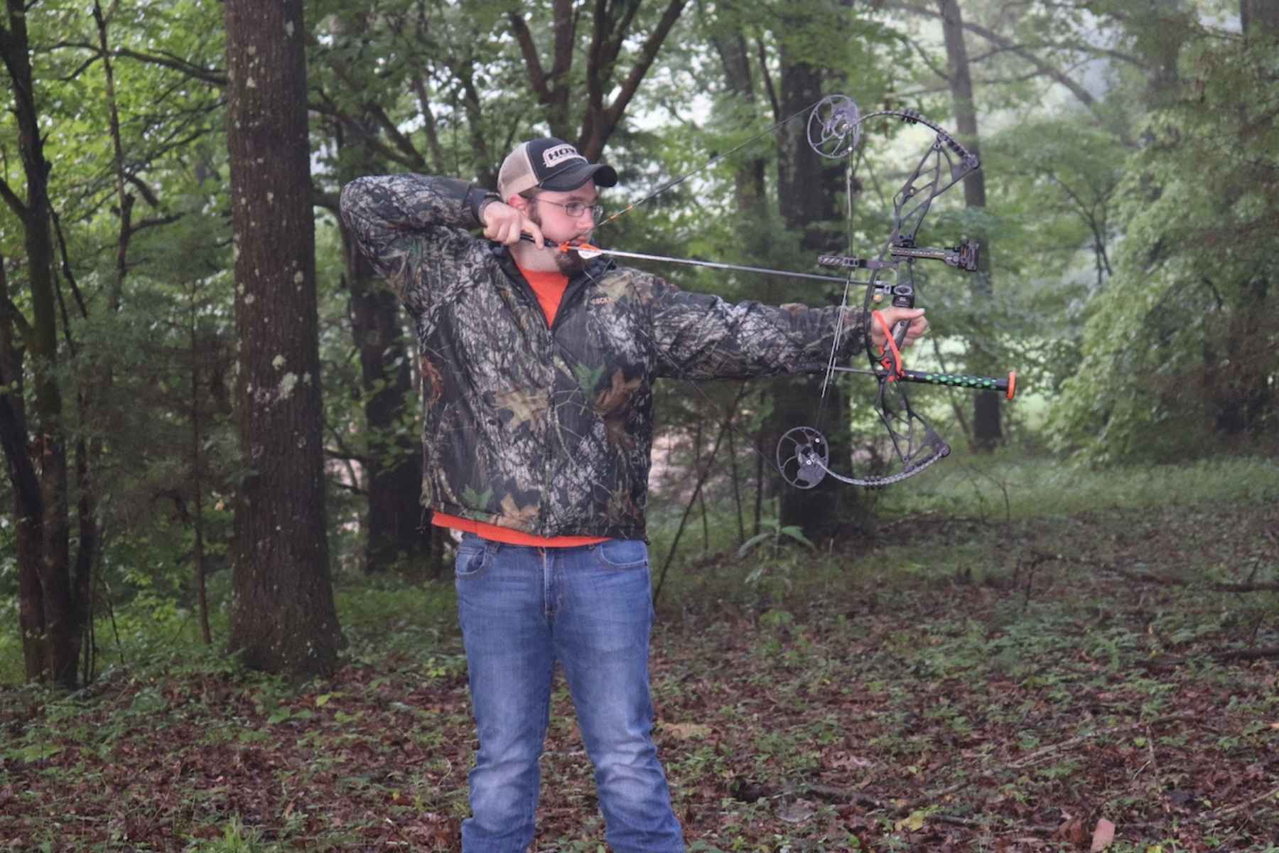 a man drawing a compound bow in the woods