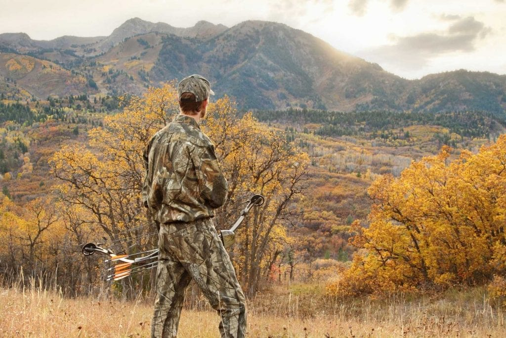 a bowhunter in camouflage, holding his bow, looking at mountains and the sunset.