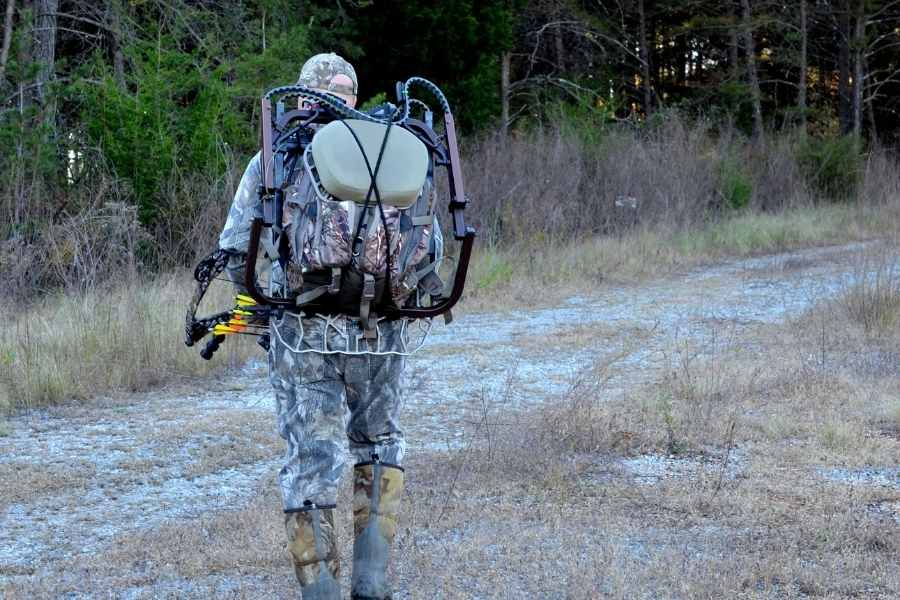bow hunter walking in the wild with a backpack and his bow