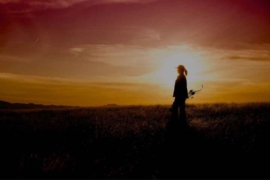 a femal archer with her recurve bow walking in the sundown