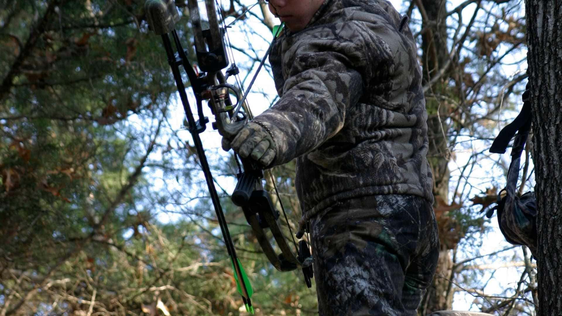 hunter in treestand aiming with bow